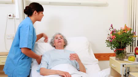 ovmak : Smiling senior patient talking with a nurse in a hospital room Stok Video