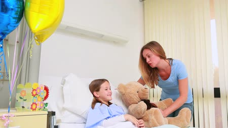 infantil : Smiling woman giving a teddy bear to a smiling girl in a hospital bed