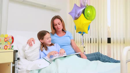 infantil : Smiling woman with her girl in a bed drawing in hospital Vídeos
