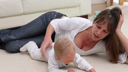 baby blue : Woman lying with a baby on the carpet Stock Footage