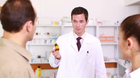 фармацевт : Pharmacist presenting a flask of pills to a couple in the pharmacy of a hospital