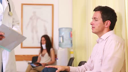 aguardando : Doctor talking to a man in a waiting room in a hospital Stock Footage