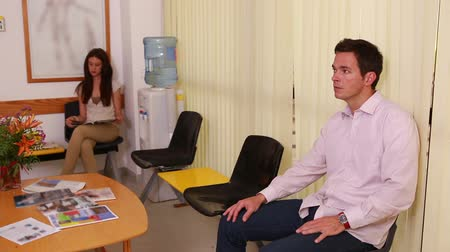 bekleme : Man shaking the hand of a doctor in a waiting room in a hospital Stok Video