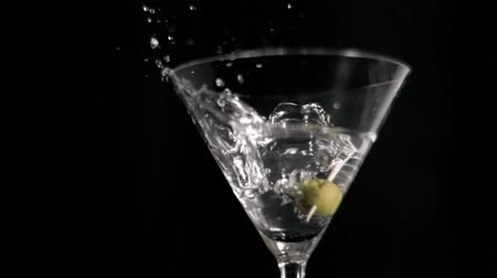 martinis : One olive falling in super slow motion in a martini against a black background