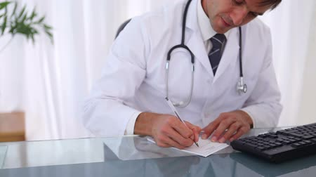 prescrição : Doctor writing a prescription in his office Vídeos