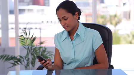 receber : Woman sending a text message in an office