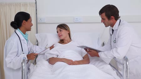 pacjent : Two doctor talking to a patient in a hospital room