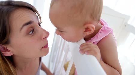 протирать : Baby girl kissing her mother in a bright room Стоковые видеозаписи