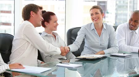 homem de negócios : Business group in an office with two shaking hands and smiling