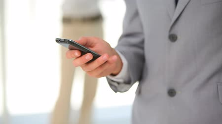redhead suit : Man in a suit typing on his phone with someone in the background Stock Footage