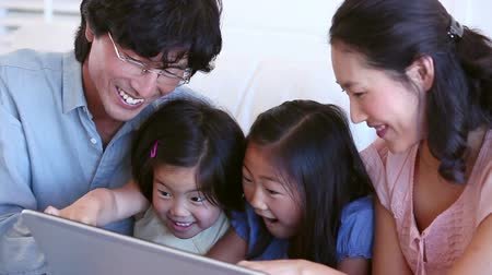 család : Family laughing while using a tablet computer in a living room