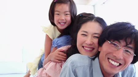 asian family : Family playfully lying on each other in a living room