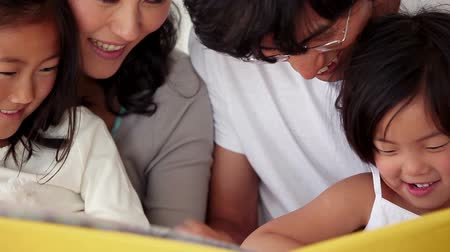 asian family : Family reading a book as they sit together in a living room Stock Footage