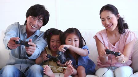 konsol : Family happily playing a games console together in a living room Stok Video