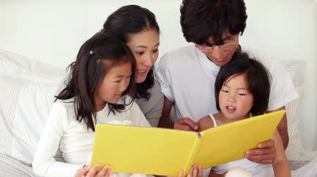 asian family : Parents reading a book to their children in a living room Stock Footage