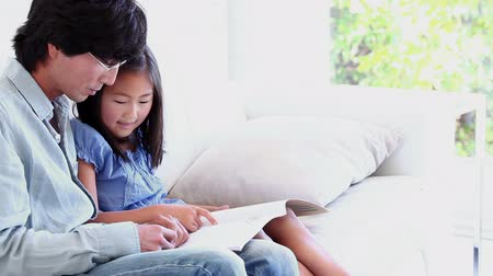 asian family : Father doing his daughters homework with her in a living room