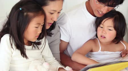 asian family : Parents reading a book to their children as they sit together in a living room