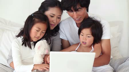 asian family : Family sitting together as they use a laptop in a living room