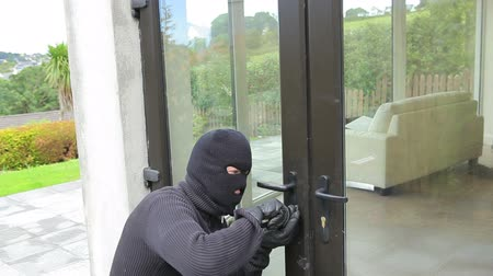 cadarço : Burglar opening lock on door and entering home