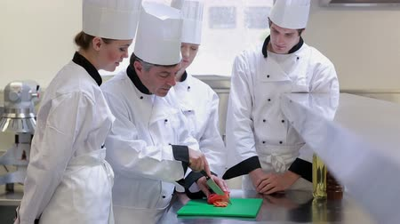 culinary : Chefs standing at a counter and learning how to slice vegetables and how to use the knife