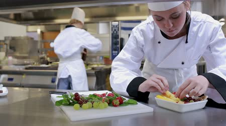preparar : Cook preparing a fruit salad at the counter of the kitchen