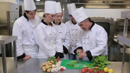 culinary : Head chef is showing the cooks how to slice vegetables and standing at a counter