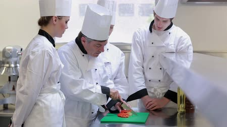 culinary : Trainne chefs learning how to slice vegetables in culinary school