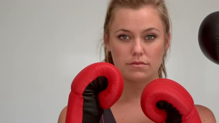 puncs : Female boxer in the guard position being hit with boxing glove Stock mozgókép