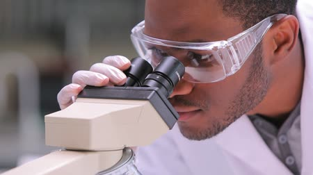 ученый : Student looking through microscope while one is watching in the laboratory