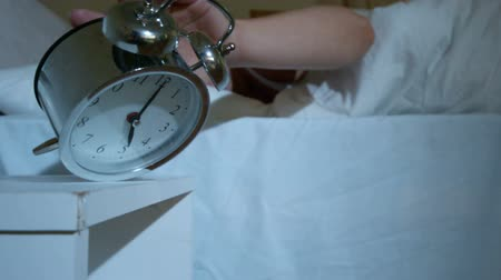 poplach : Blonde lazy woman in bed knocking over alarm clock