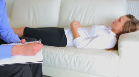 terapeuta : Woman lying on the sofa at a therapists office Stock Footage