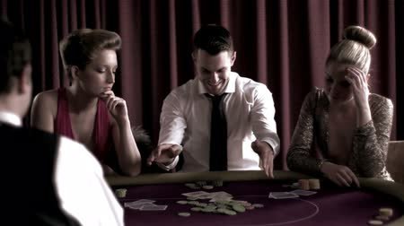 zengin : Brunette man winning against two girls at poker table Stok Video