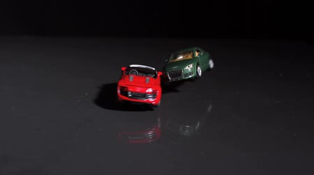 toy : Red toy car crashing into green toy car in slow motion