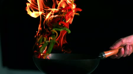 chef cooking : Peppers flaming in the pan in slow motion Stock Footage