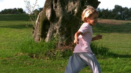 quintal : Girl child running around after a large tree in slow motion