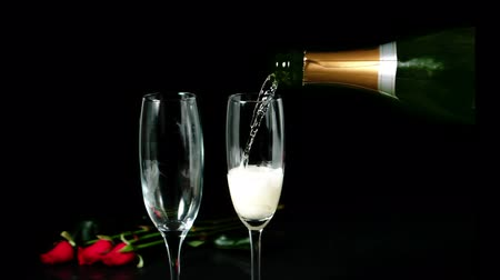 šampaňské : Champagne pouring on a flute with roses behind it in slow motion Dostupné videozáznamy