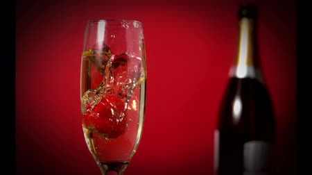 šampaňské : Strawberry falling in the flute with a champagne bottle on background in slow motion