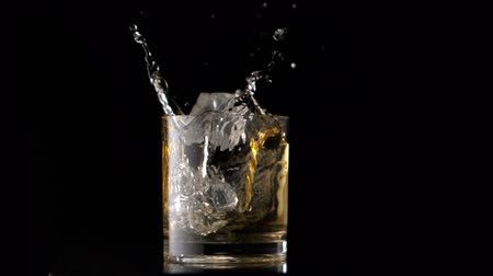 viski : Ice cubes falling into whiskey in slow motion Stok Video