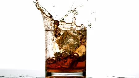 viski : Ice cube falling in whiskey tumbler on white background in slow motion