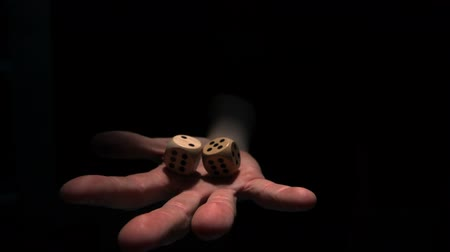 dobókocka : Hand grasping wooden dice in slow motion