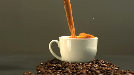 xícara de café : Coffee being poured into cup on mound of coffee beans in slow motion