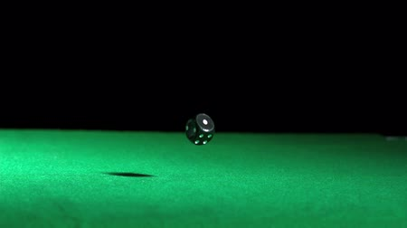 dobókocka : Black dice falling and bouncing on green table in slow motion Stock mozgókép