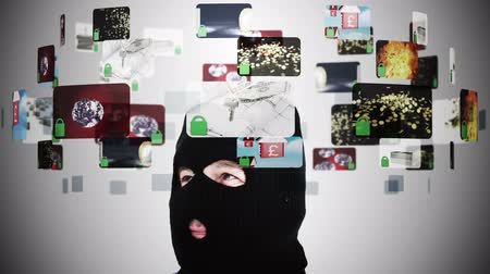 przestępca : Criminal in balaclava contemplating various security situations displayed in holographic interface Wideo