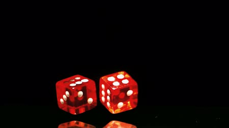 dobókocka : Two red dice falling and bouncing close up on black background in slow motion