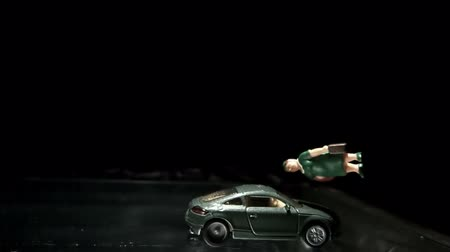 baleset : Green toy car crashing into a woman figurine in slow motion
