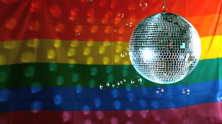 гей : Shiny disco ball turning with floating bubbles against rainbow flag in slow motion