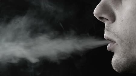 carcinogenic : Man smoking cigarette in black and white on black background