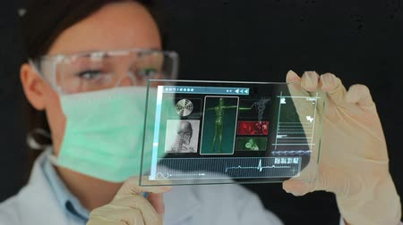 Scientist using futuristic touchscreen technology to view medical clips Стоковые видеозаписи