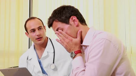 sitting room : Doctor talking to a man while they sit in a waiting room in a hospital Stock Footage