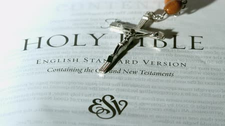 jehovah witness : Rosary beads falling onto first page of the holy bible in slow motion